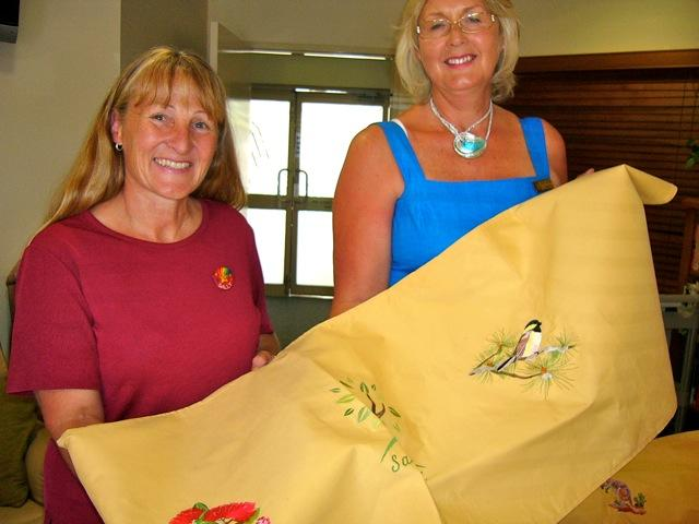 SI member Maggie Thatcher presents the quilts to Sally Harris Clinical Co-ordinator of Sandalwood Hospice